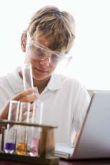 A student with a laptop holding a test tube