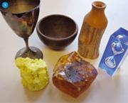Figure 5 - Miscellaneous objects: a silver goblet, a wooden bowl, manuka wooden vase, Perspex hour glasss, kauri gum and a lump of natural sulfur