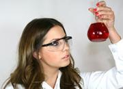 A scientist looking closely at a flask filled with red liquid