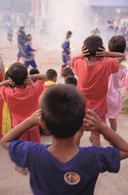Children cover their ears as firecrackers go off at a bangkok temple