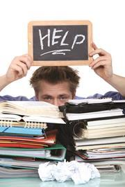 Holding up a 'help' sign above a stack of revision files