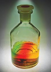 A reagent bottle with a three-colour liquid
