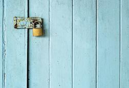 Metal padlock on blue door