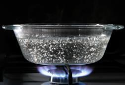 A glass dish of boiling water on a gas hob