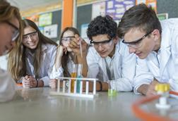 A group of A-level students doing a practical experiment, boy using a pipette to add to a test tube.