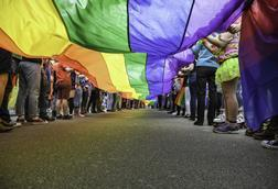 A long rainbow flag being held by two rows of people, seen from below