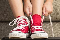 Child tying shoelaces on red American sneakers
