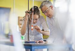 A photo showing a chemistry teacher helping a student with a titration