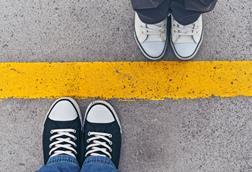 Two pairs of feet either side of a painted, yellow line on the ground
