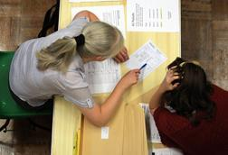 An image showing a female teacher and a student inspecting A level results, shot from above, no faces visible