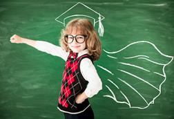 Small girl wearing glasses with arm outstretched in front of a blackboard, where a mortar board and academic cape are drawn