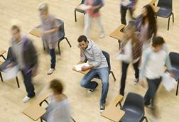 An image showing college students moving around man at desk in a classroom