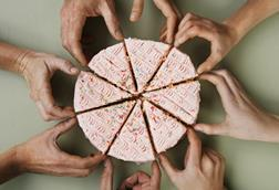 A picture showing a pink-iced cake, cut into eight, a hand going to pick up each piece