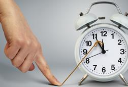 A forefinger holds down a string attached to the big hand of an alarm clock, effectively stopping time
