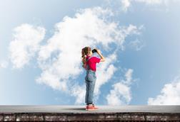 Girl looking into the sky with binoculars