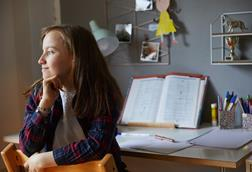A picture showing a girl sitting on a chair and gazing out of the image, behind her is a desk with lamp, books and pens