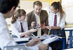 An image showing a teacher explaining chemistry concepts with the help of a molecular model to his students