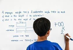 An image showing a child (wearing a blue T-shirt) solving a maths problem using the bar model on a whiteboard