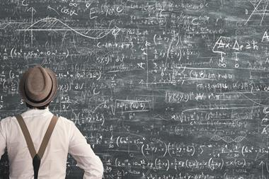 Man standing in front of large blackboard covered in confusing equations