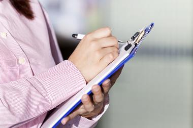 An image showing a woman taking notes on a clipboard
