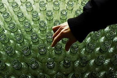A hand examines clear glass bottles