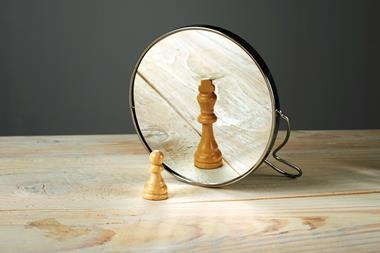 A pawn before a mirror, reflected as a king