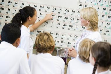 An image showing a teacher in front of a periodic table, surrounded by students, all with their backs to camera; a female student is pointing at the element cobalt.