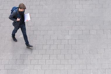 A top view of a student dressed in blue carrying a rucksack walking across grey paving stones, from left to right