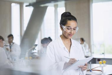An image showing a female student writing notes in a notebook she's holding; she is wearing a lab coat and lab spectacles, and the background is a school science laboratory