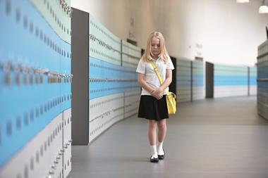 An image showing a shy female student wearing school uniform with a yellow satchel walking with her head down on a corridor lined by blue and grey lockers