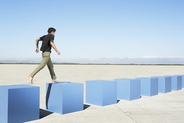 Male student barefoot walking from one blue block to another, with six more in front of him, on a concrete floor against a blue sky. Representing moving from stage to stage in an intelligent learning platform