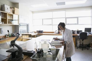 A picture showing a female technician wearing a white lab coat in a school laboratory with a textbook, microscope and fume cupboard visible