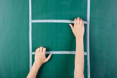woman's hands on different rungs of a ladder drawn on a green chalkboard