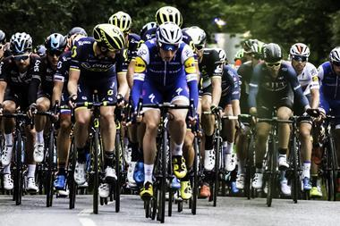 A dozen male cyclists in a tight grouping pictured from the front