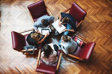 Five teachers sat in red armchairs collaborating. Shot from above. Parquet floor