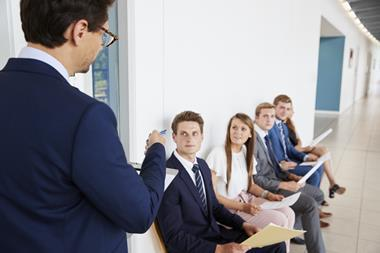 Four young professionals sitting in the corridor as a man class one in for interview