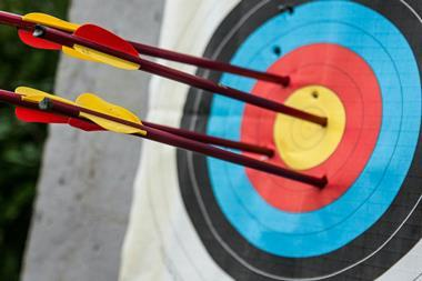 Four arrows embedded in an archery target