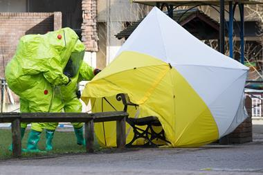 Two people in Hazmat suits around a bench covered in plastic