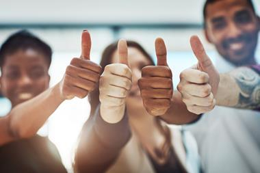 Four people with thumbs up