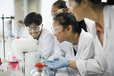 Four students wearing lab coats, safety goggles and gloves work at a lab bench