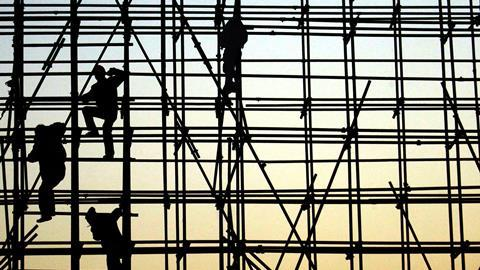 Workers climbing scaffolding in silhouette