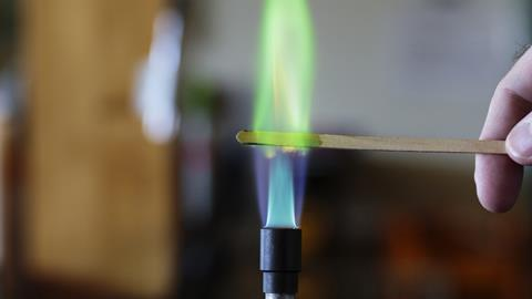 Copper solution burning on a wooden splint in a bunsen burner flame, producing a green flame