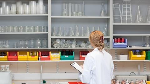 Female lab tech with clipboard looking at lab equipment