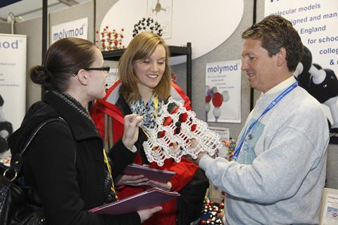 An image showing teachers inspecting a molecular model during the ASE conference