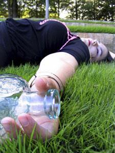 A person passed out on the ground, holding a bottle