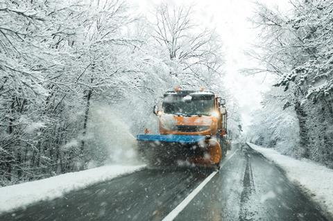 A snow plough clearing snow from a road