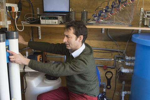 Scientist with water purification equipment and laptop in shed