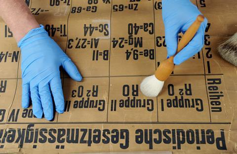 Shot from above, two hands wearing blue gloves are using a brush to gently remove surface dirt from an old document, the oldest classroom periodic table