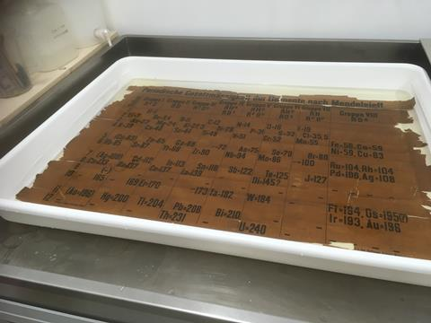 A metal workbench holds a white shallow tray, filled with a liquid and an old document, the oldest classroom example of the periodic table