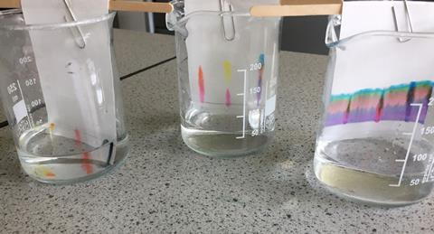 An image showing three thin layer chromatography plates; each is suspended in a measuring flask using a lolly stick and paper clip, the flasks are all on a workbench.